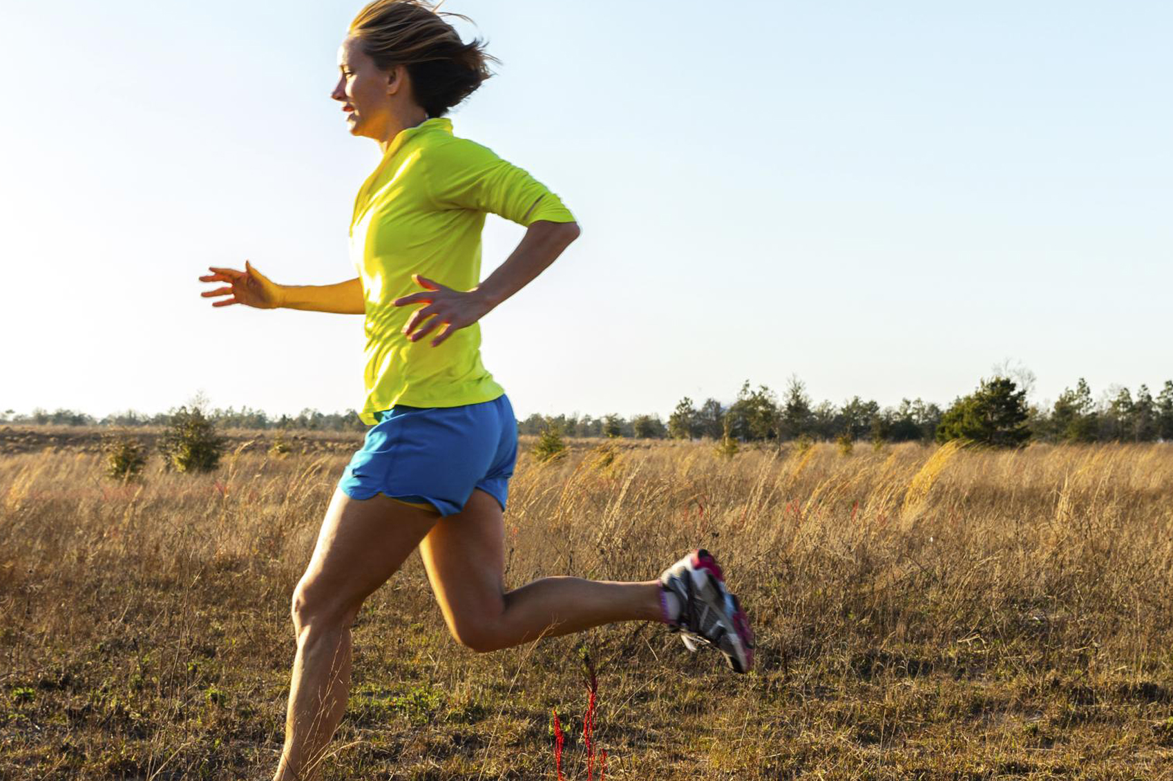 A woman jogging on a path in a field.